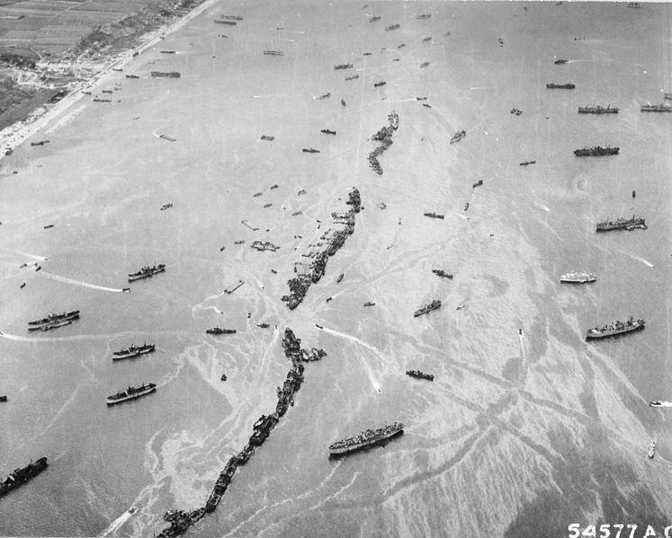 """Sztuczny falochron utworzony poprzez zatopienie 13 transportowców typu """"Liberty"""". Źródło: Wikimedia Commons, domena publiczna."""