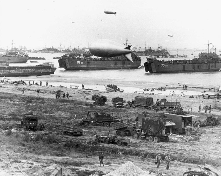 Czasochłonny i skomplikowany rozładunek okrętów transportowych LST w 1944 roku w Normandii, prawdopodobnie 7 czerwca. Sztuczny port Mulberry umożliwiał cumowanie okrętów i szybszy rozładunek okrętów typu LST, bez konieczności osadzania ich na dnie. Źródło: Wikimedia Commons, domena publiczna.