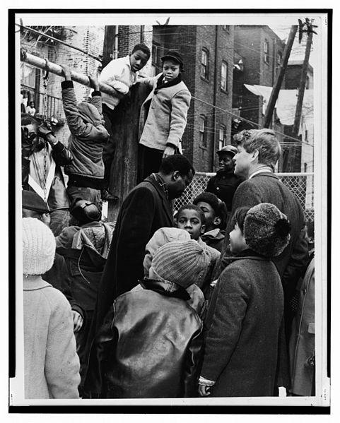 Senator Robert Kennedy z grupą czarnoskórych dzieci z ubogiej dzielnicy. Fot. Dick DeMarsico, źródło: Wikimedia Commons, domena publiczna.