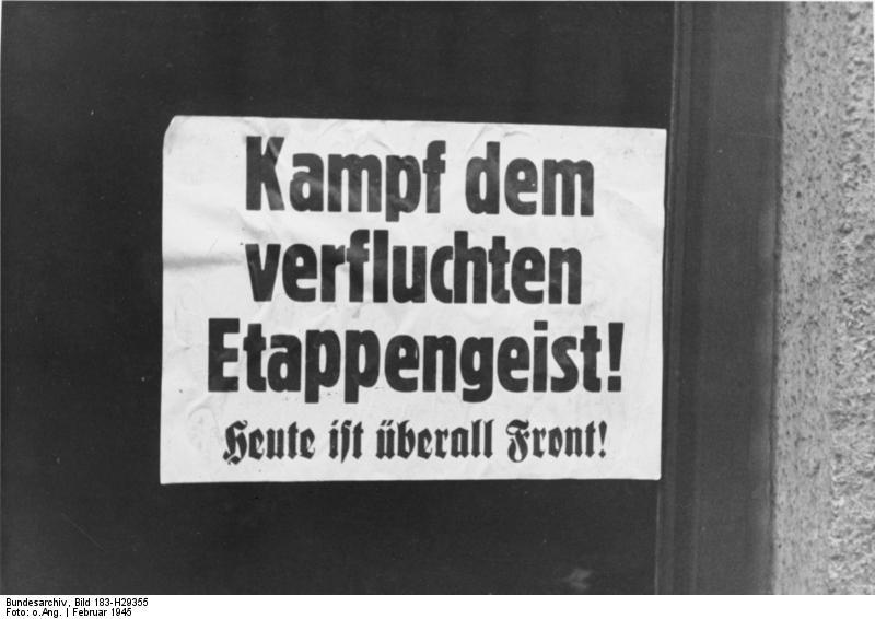 """Wywieszony we Wrocławiu plakat propagandowy z lutego 1945 roku. """"Walcz z przeklętym duchem tyłów! Dzisiaj wszędzie jest front!"""" (Określenie Etappengeist oznaczało defetystyczną postawę wykazywaną na tyłach frontu, często przez żołnierzy chcących za wszelką cenę uniknąć walki, tzw. dekowników, określanych jako """"świnie etapowe"""" - """"Etappenschweine"""". Samo określenie """"Etappen"""" w armii niemieckiej wywodzi się jeszcze z XIX wieku i oznacza etapowy system logistyczny zaopatrzenia frontu i organizacji jego tyłów. Przeciwieństwem dla """"Etappengeist"""" był """"Kampfgeist"""", promowany przez nazistowską propagandę niezłomny """"duch walki"""". Przyp. red.) Źródło zdjęcia: Bundesarchiv, Bild 183-H29355 / CC-BY-SA 3.0"""